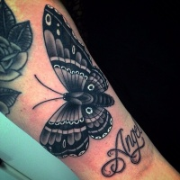White and black moth tattoo on girls wrist