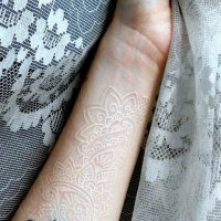 White ink lace and black spider forearm tattoo