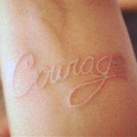 White ink lettering courage tattoo on wrist