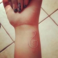 White ink treble clef tattoo on wrist