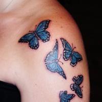 bianca con blu piccole farfalle tatuaggio su spalla