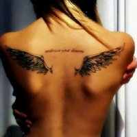 Wings tattoo and inscription tattoo on back