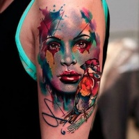 Wonderful colored watercolor style abstract woman portrait tattoo on shoulder combined with small bird
