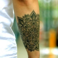 Wonderful geometric style designed big black and white flower tattoo on arm
