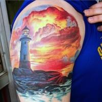 splendido disegno multicolore  faro su mare tramonto tatuaggio su spalla