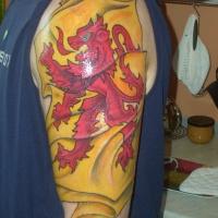 Gelbes und rotes schottisches  Tattoo an der Schulter