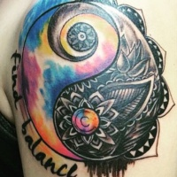 Yin Yang symbol shaped shoulder tattoo stylized with various flowers and lettering