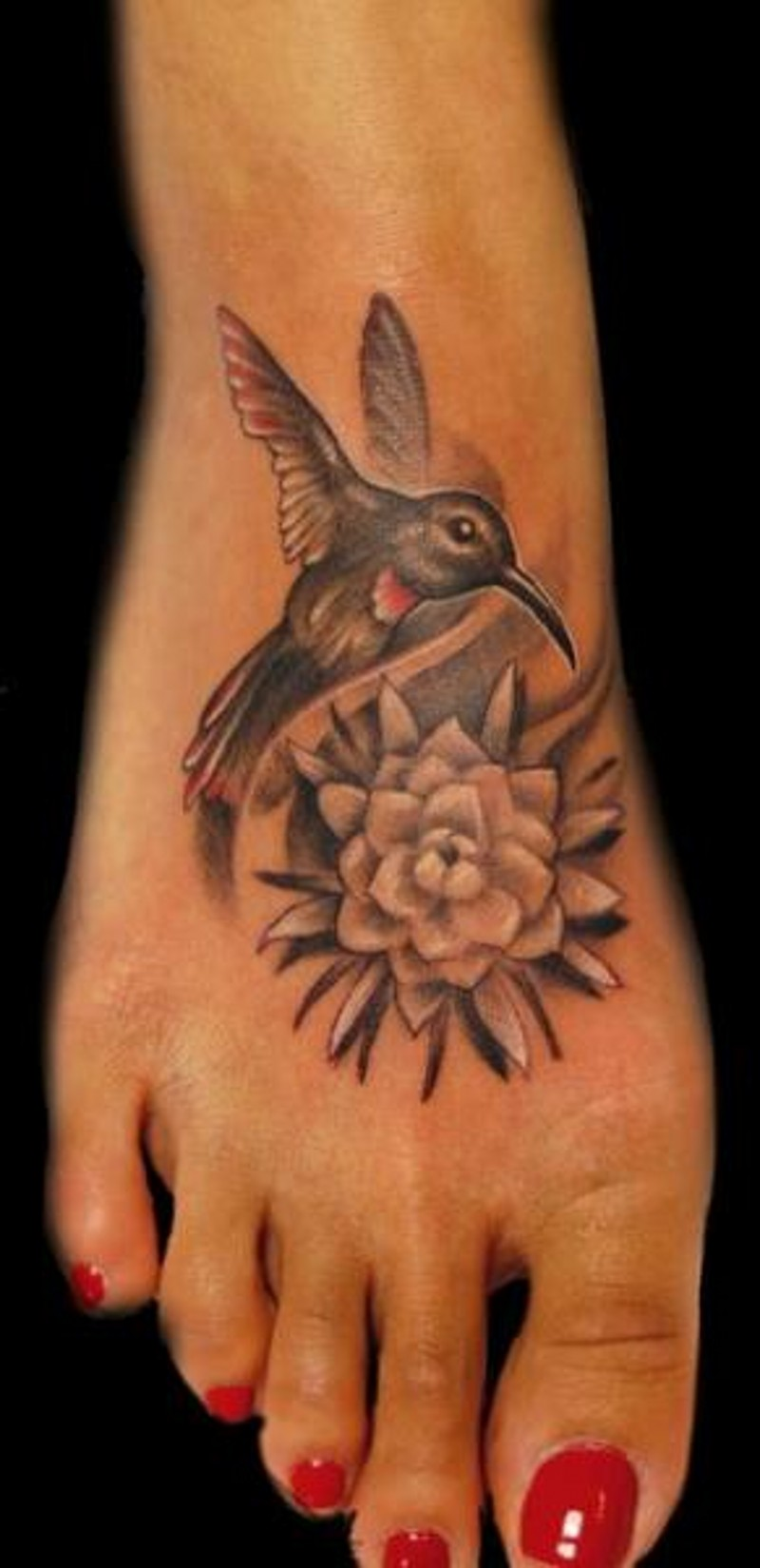 Tiny beautiful colored foot tattoo of hummingbird with flower