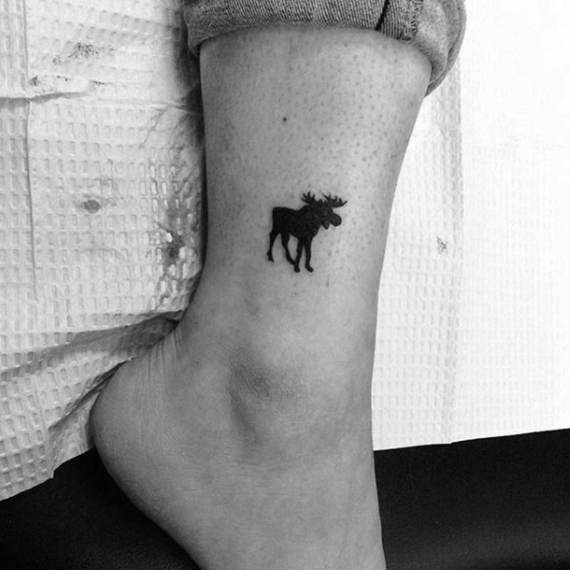 Tiny black ink ankle tattoo of homemade like elk