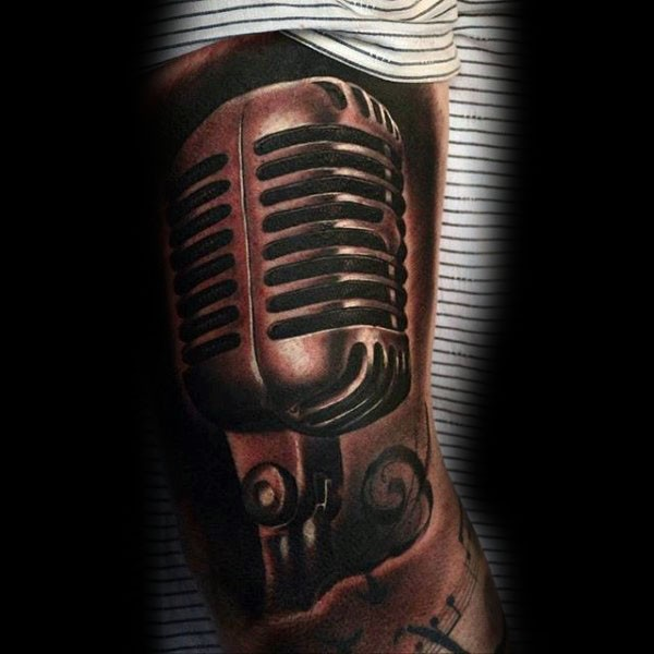 Tiny black ink detailed vintage microphone tattoo on arm