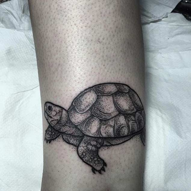 Tiny black ink funny turtle tattoo on arm muscle