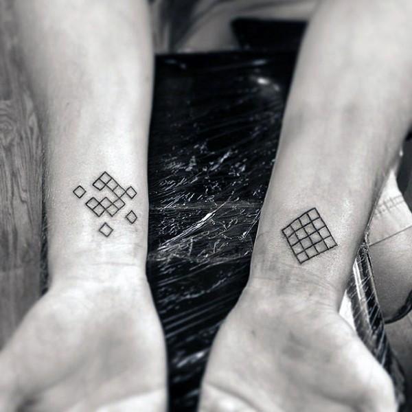 Tiny black ink geometrical tattoo on wrists