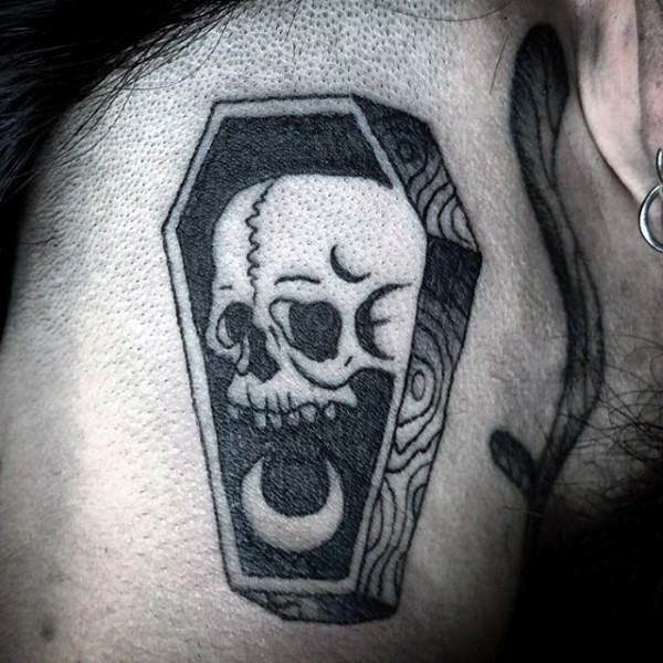 Tiny black ink little wooden coffin with skull tattoo on shoulder