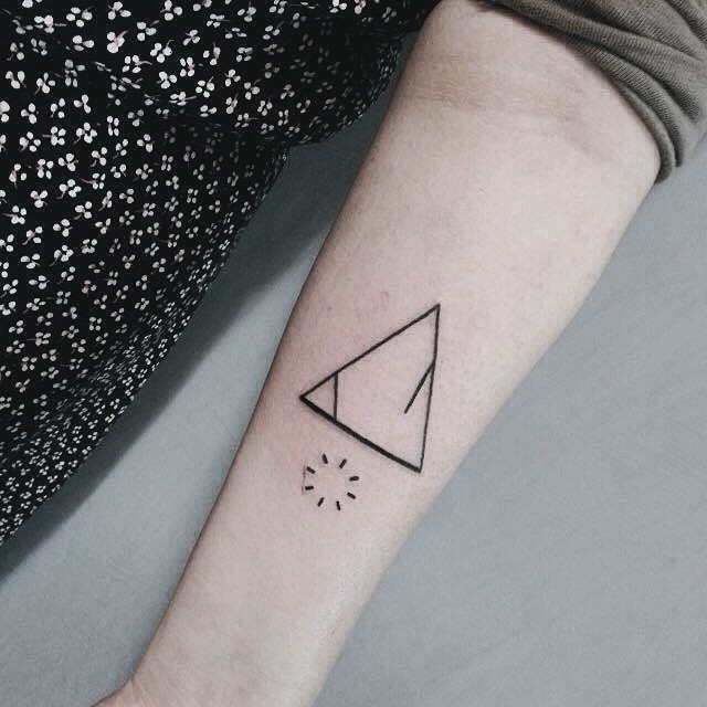 Tiny black ink mystical triangle tattoo on forearm with interesting circle shaped symbol