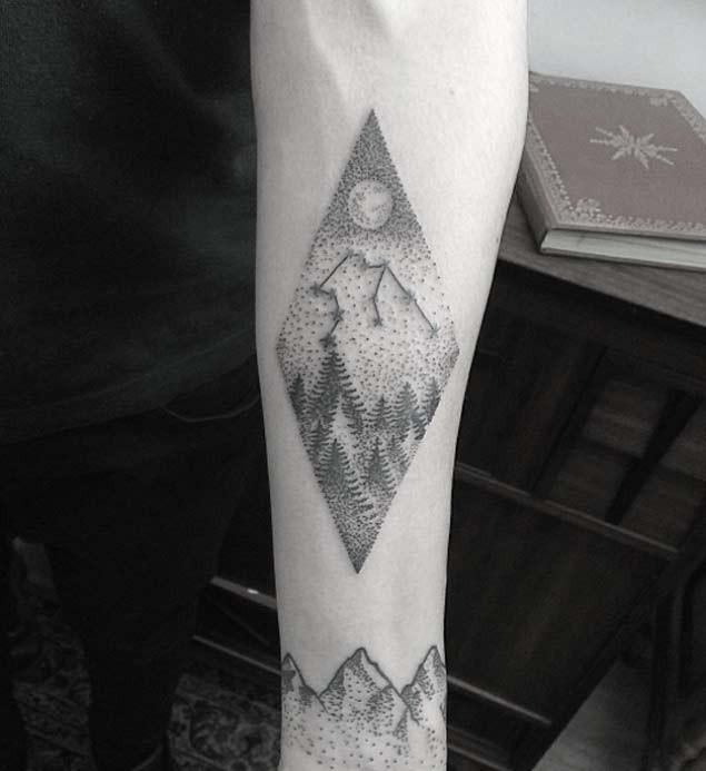 Tiny black ink zodiac symbol tattoo on forearm stylized with night sky and forest