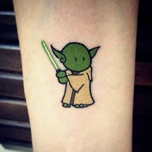 Tiny cartoon like little funny master Yoda with light saber tattoo on forearm area