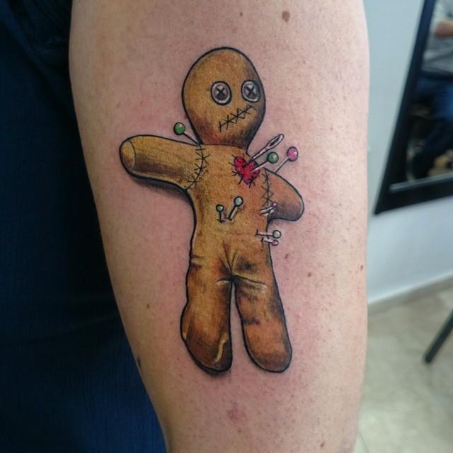 Tiny cartoon like Voodoo doll tattoo on arm
