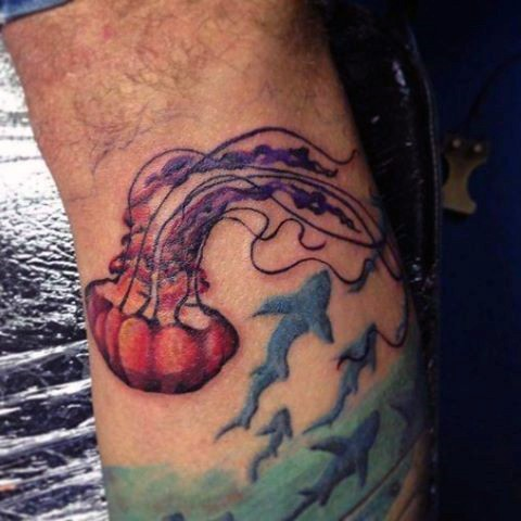 Tiny homemade like colorful jellyfish with sharks tattoo on leg