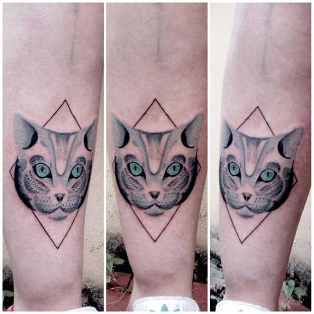 Tiny mystical painted cat face tattoo with blue eyes and geometrical figure