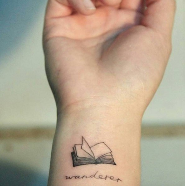 Tiny open book detailed wrist tattoo with lettering wanderer