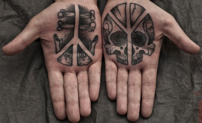 Tiny stippling style hands tattoo of human skull with bones