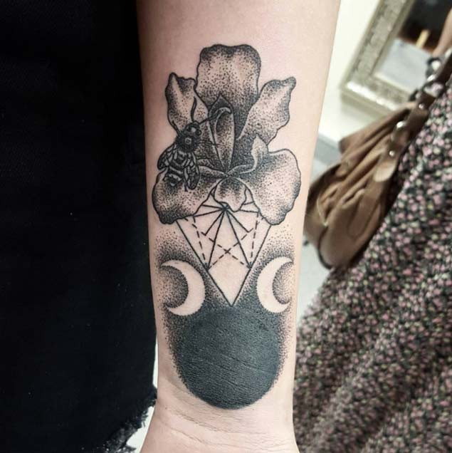 Tiny strange combined black ink cult forearm tattoo of flower with bee and dark planet with moons