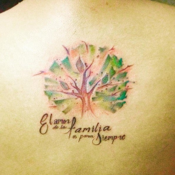 Tiny sweet painted colorful little tree tattoo on back stylized with lettering