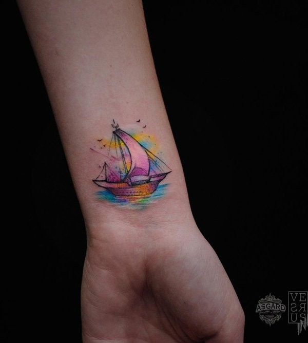 Tiny watercolor style wrist tattoo of small sailing ship