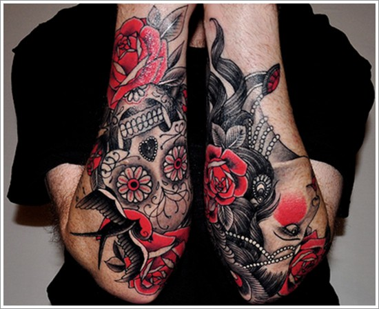 Traditional Mexican style painted flowers with skull tattoo on arms