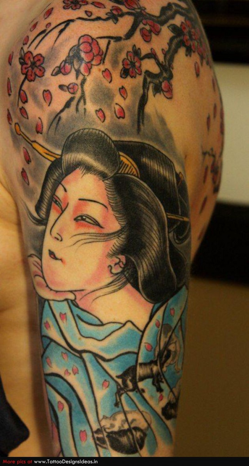 Traditional painted colored geisha tattoo on shoulder with blooming tree