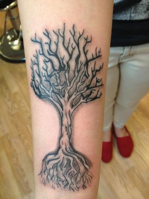 Tatuaggio carino sul braccio l&quotalbero con la radice