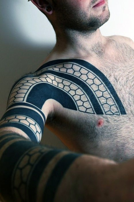 Tribal style black and white detailed geometrical tattoo on chest and sleeve