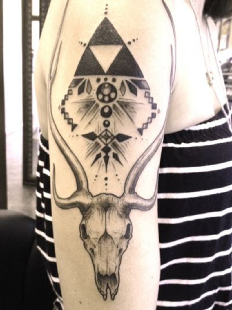 Tribal style black and white pyramid shoulder tattoo with animal skull