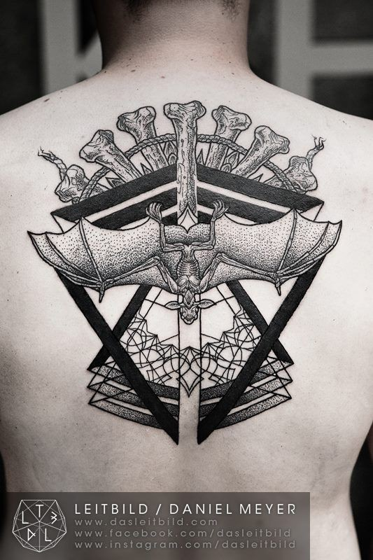 Tribal style black and white totem with bat tattoo on upper back