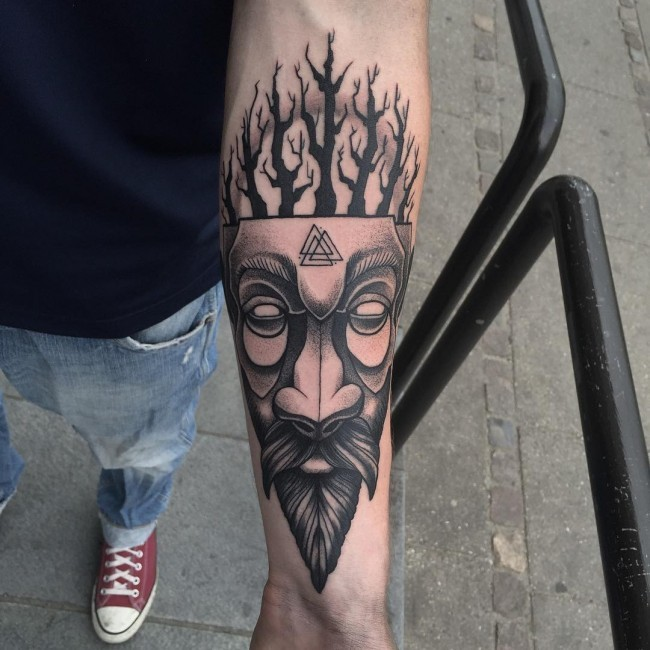 Tribal style black in mask tattoo on forearm stylized with triangle shaped symbols and trees