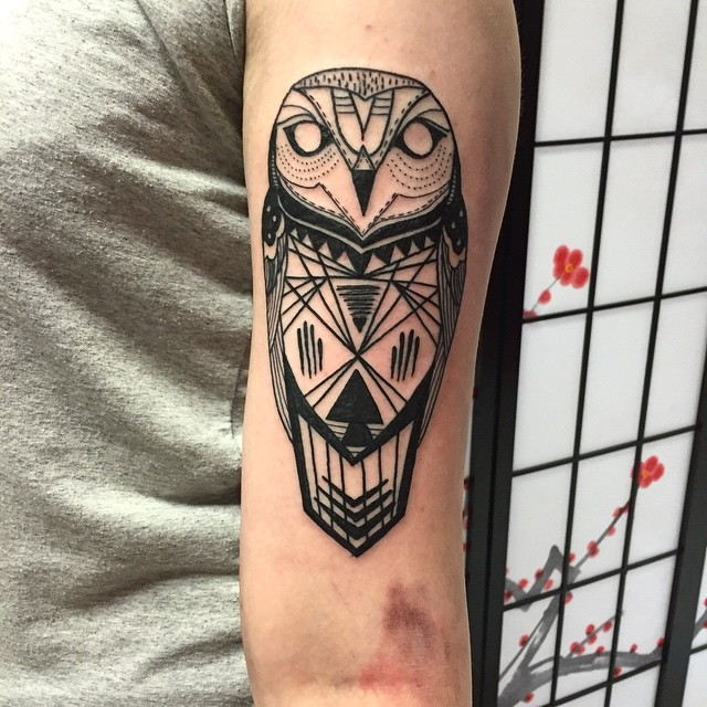 Tribal style black ink arm tattoo of owl
