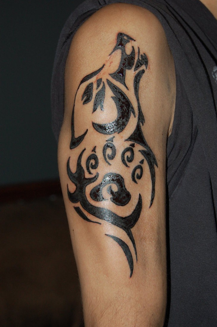 Tribal style black ink shoulder tattoo of wolf