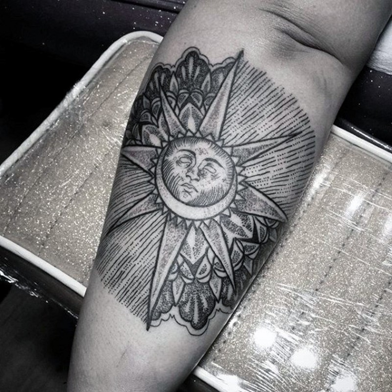 Tribal style black ink sun with moon tattoo on arm