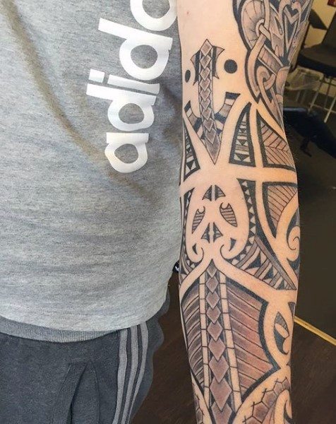 Tribal style colored original ornaments tattoo on sleeve