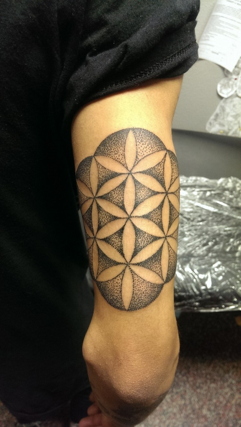 Tribal style designed black ink flower shaped tattoo on arm