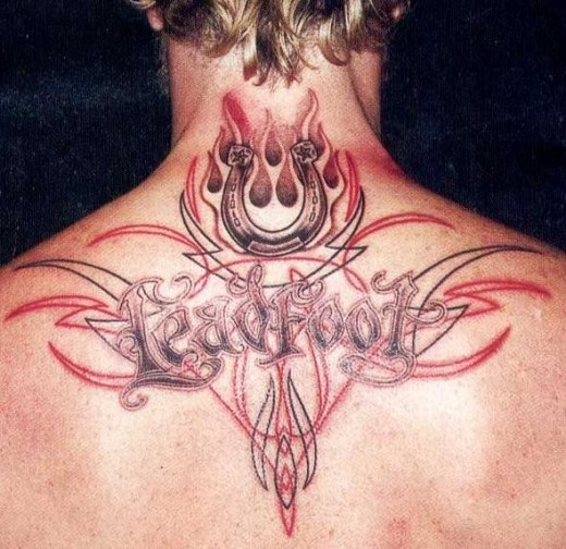 Tribal style multicolored tattoo with horseshoe and lettering on upper back