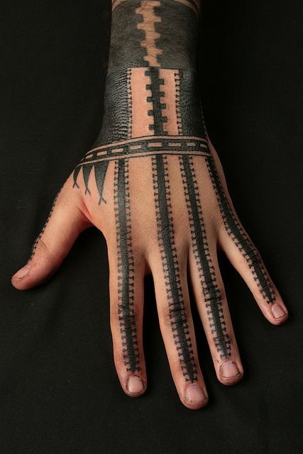 Tribal style simple designed big black and white ornaments tattoo on hand