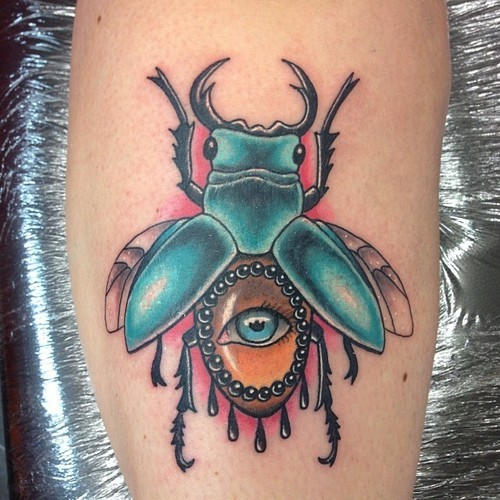 Turquoise beetle with human eye on abdomen tattoo