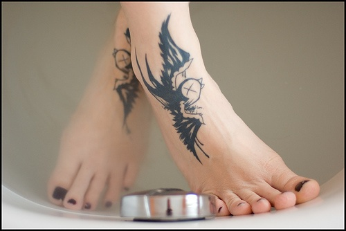 Two black swallows flying foot tattoo