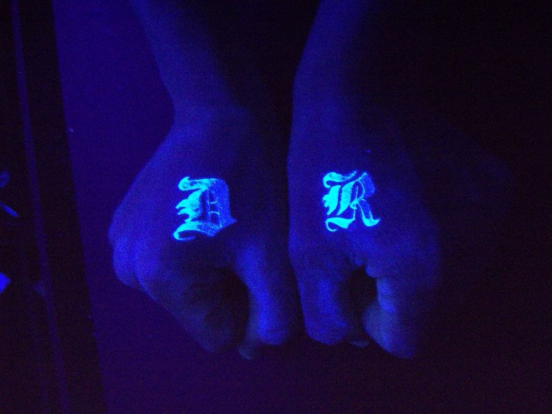 Two signs black light hand tattoo