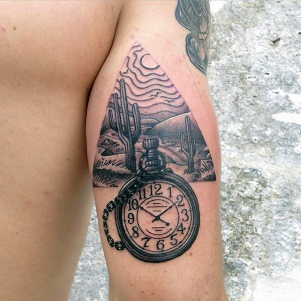 Typical black and gray style arm tattoo of triangle shaped desert picture and old clock
