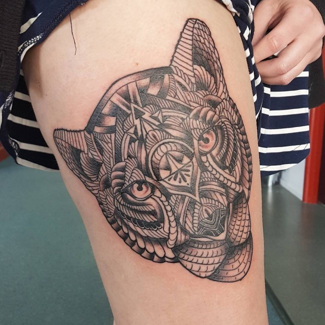 Typical black and gray style thigh tattoo of lion head stylized with various ornaments