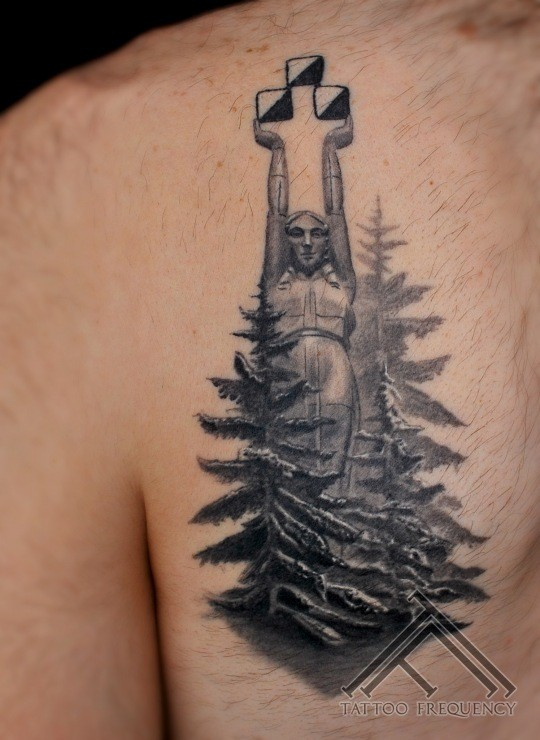 Typical black ink chest tattoo of big stone statue with forest
