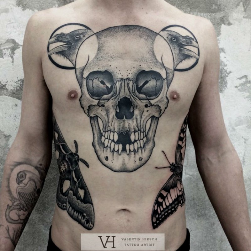 Typical black ink chest tattoo of human skull with crows