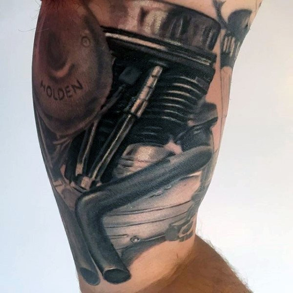 Typical black ink detailed engine tattoo on arm
